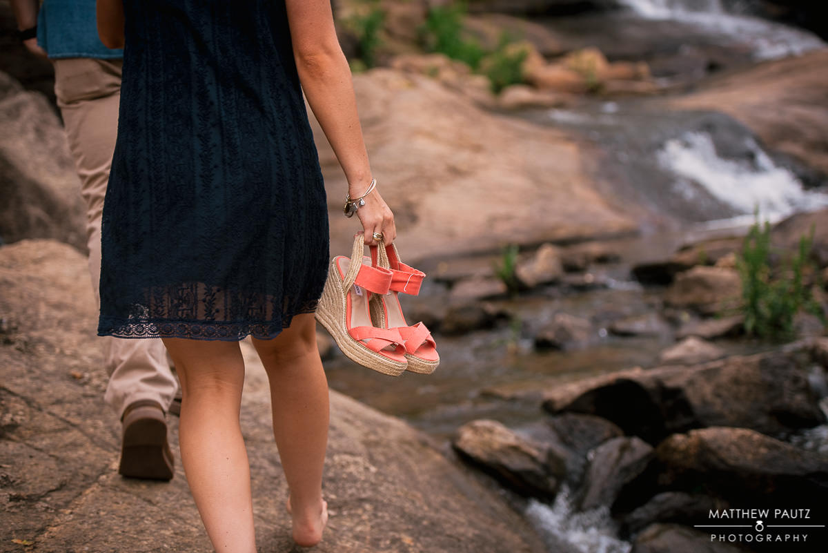 woman holding shoes while walking with fiance next to Reedy River