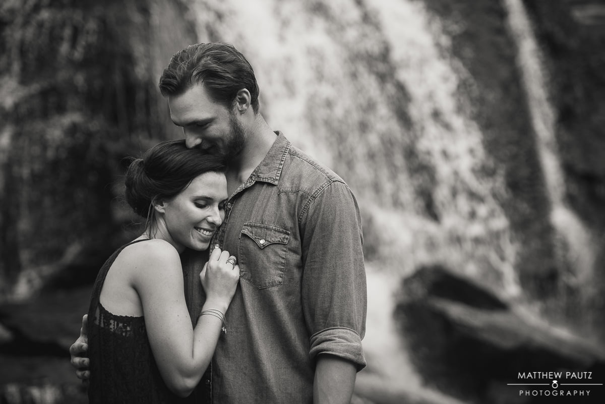 Engaged couple hugging in front of Reedy River Falls