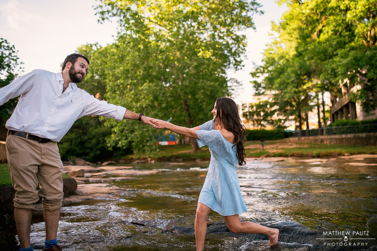 woman pulling fiance into river during engagement photos
