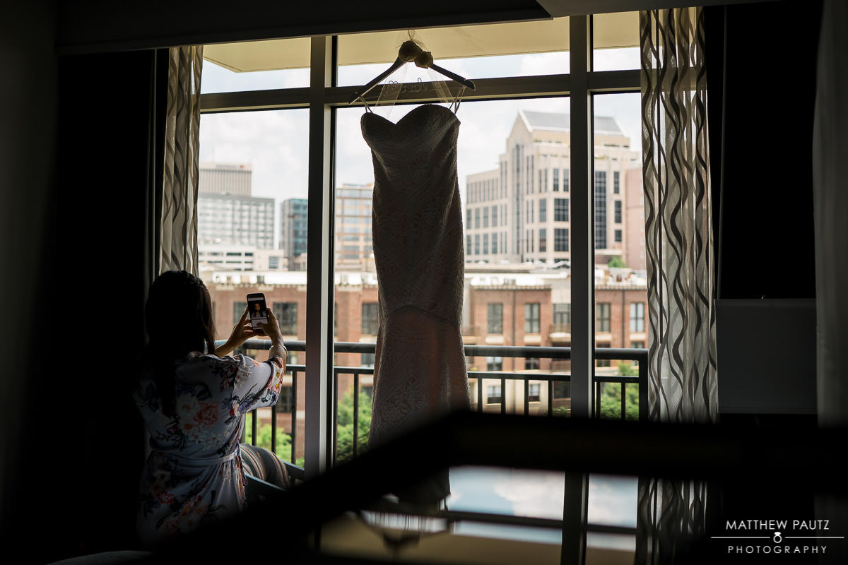 bridesmaid taking photo of wedding dress hanging in window