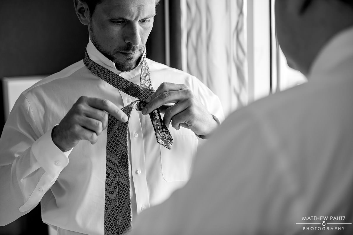 groom tying tie before getting dressed