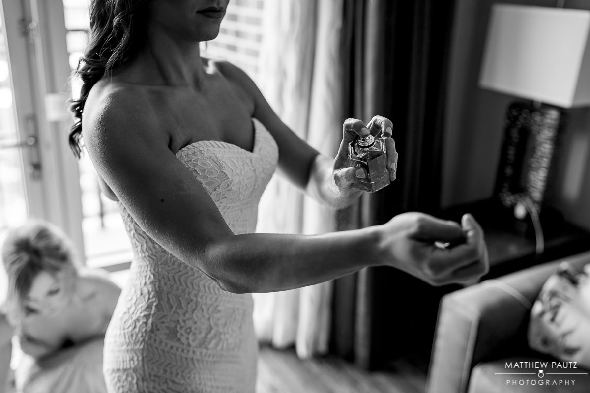 bride spraying perfume on wrist after getting dressed