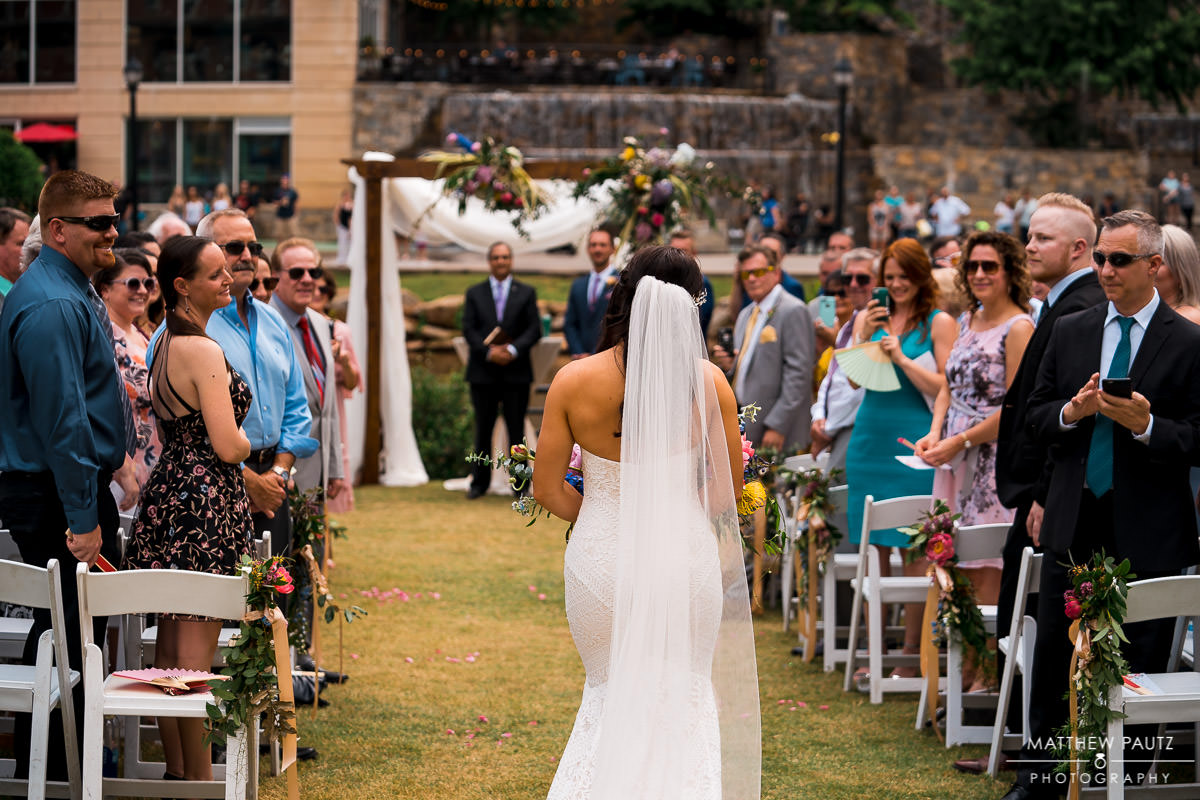 Bride walking down aisle alone at wedding ceremony
