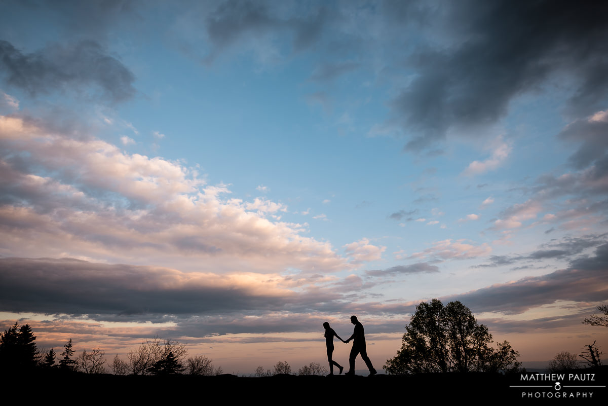 Silhouetted couple walking at sunset in mountains