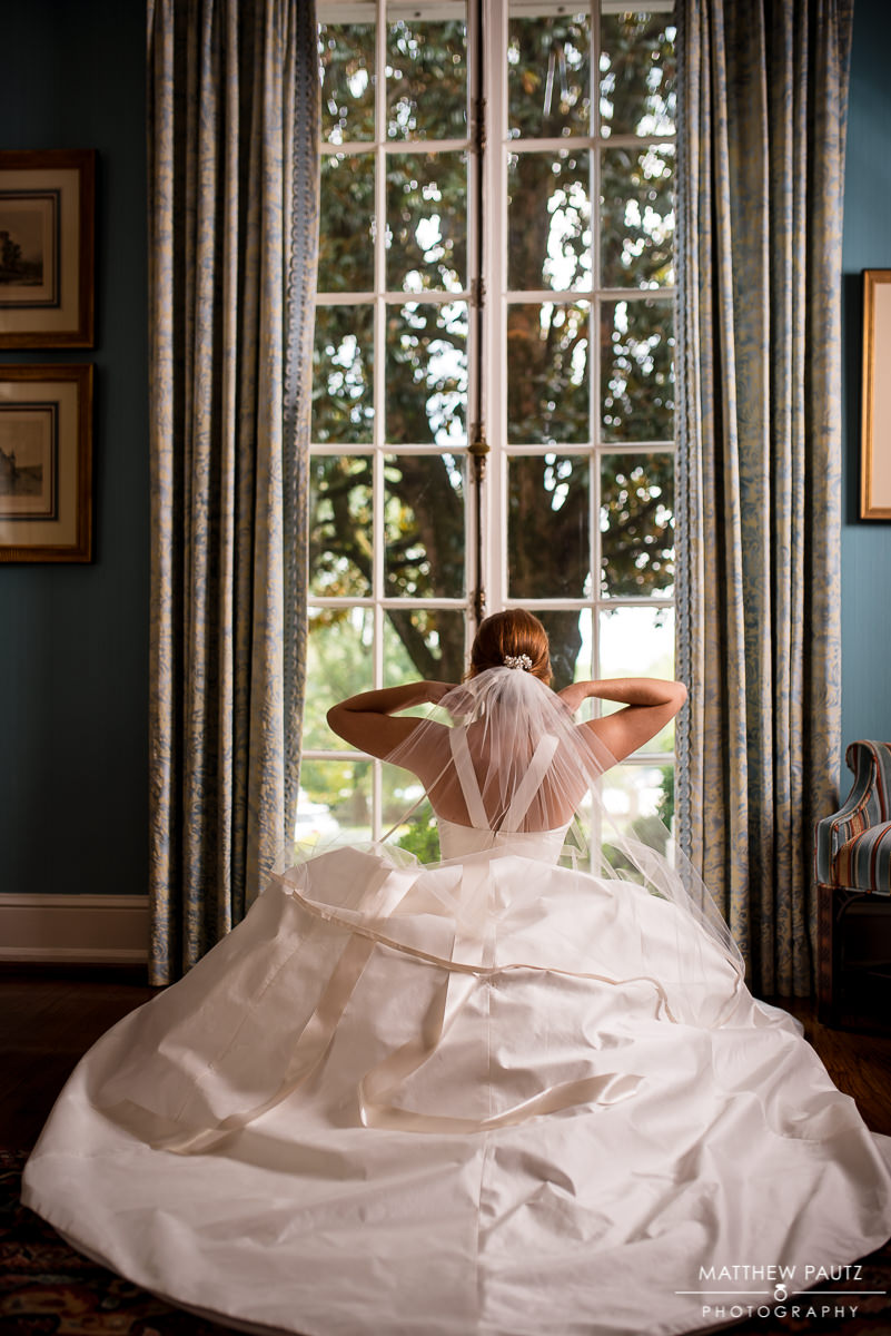 Bride in wedding dress posing in front of window at The Poinsett Club