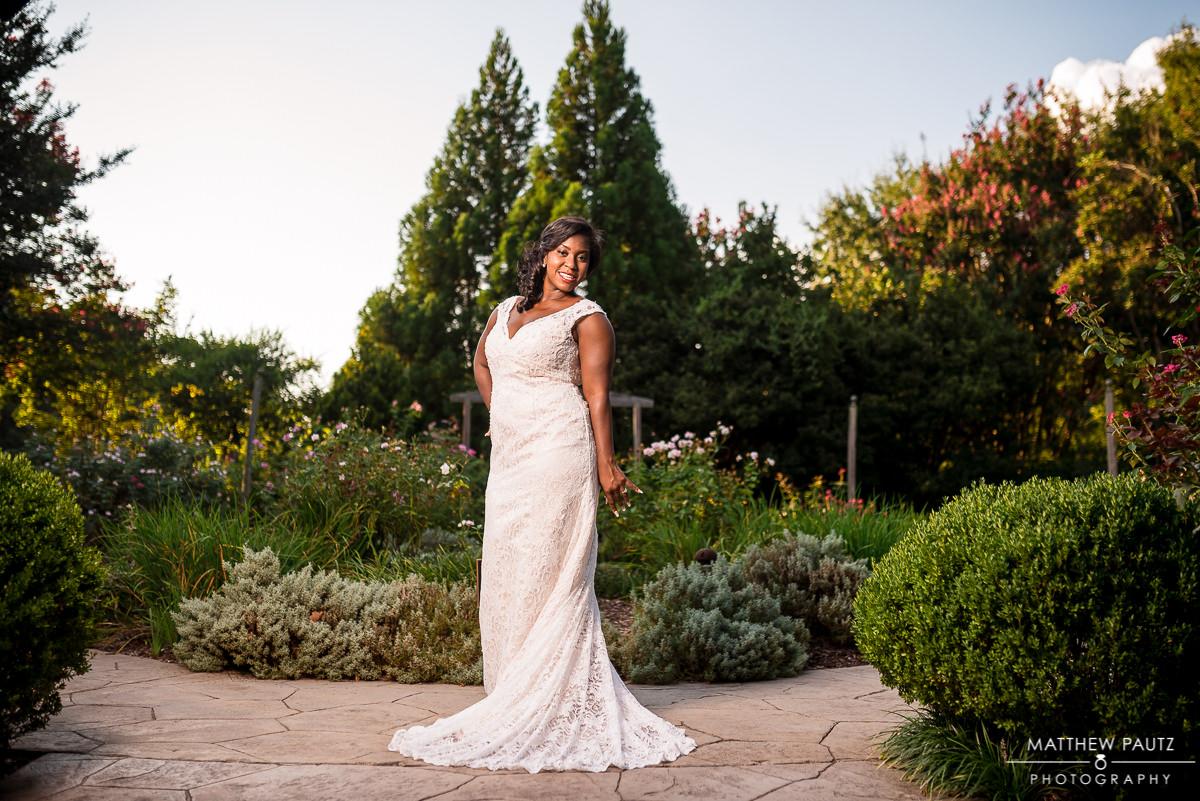 Bride posing in wedding dress in botanical garden