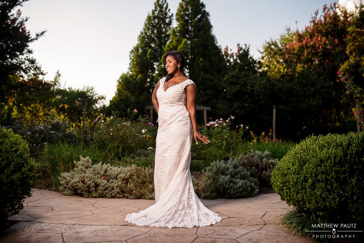 bride smiling happily in wedding dress in garden