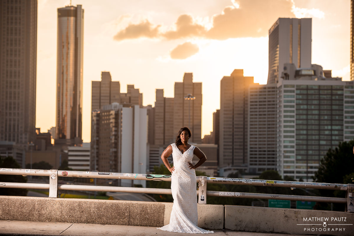 bride posing in wedding dress on jackson street bridge in Atlanta