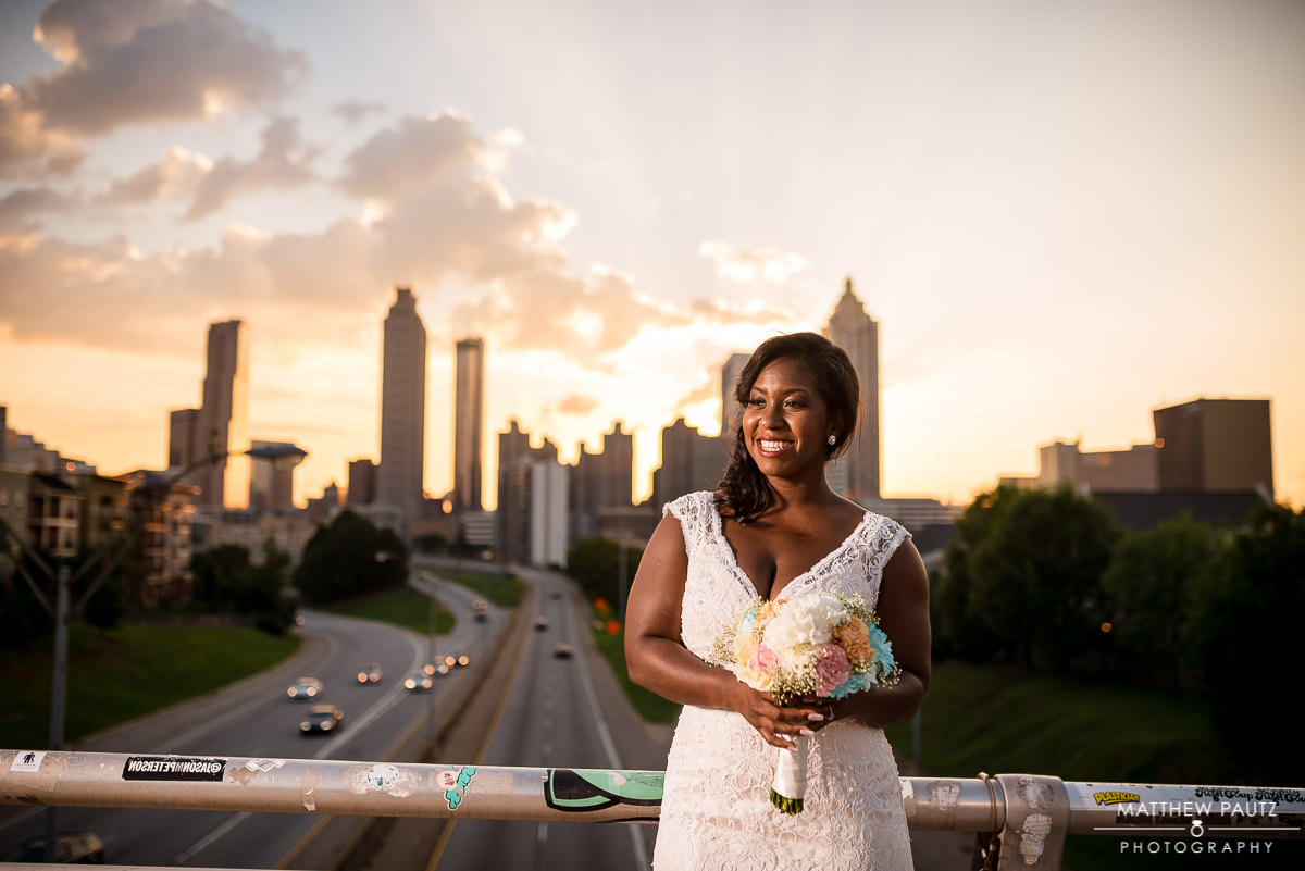 bride holding flowers on jackson street bridge in Atlanta