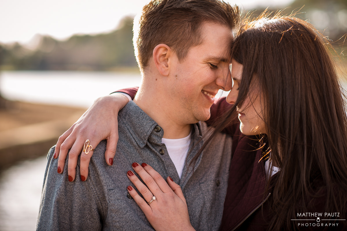 closeup of engaged couple hugging at sunset