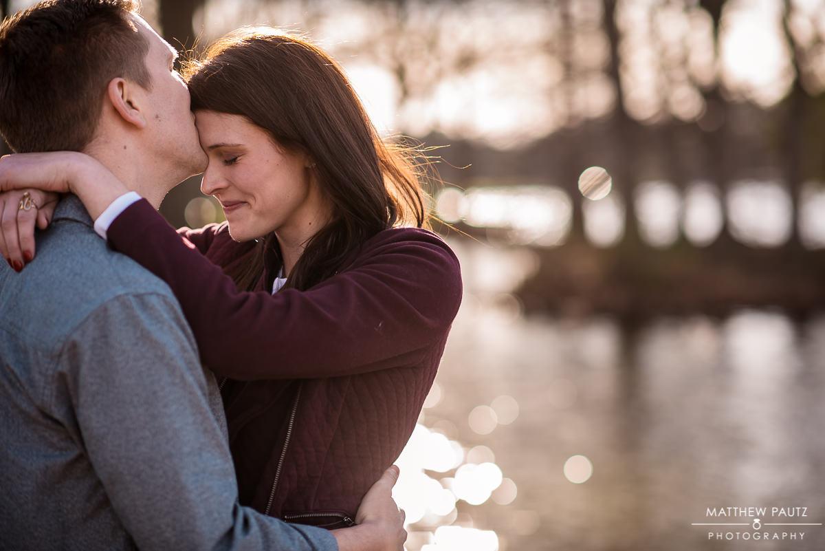 man kissing woman on forehead at the lake at sunset