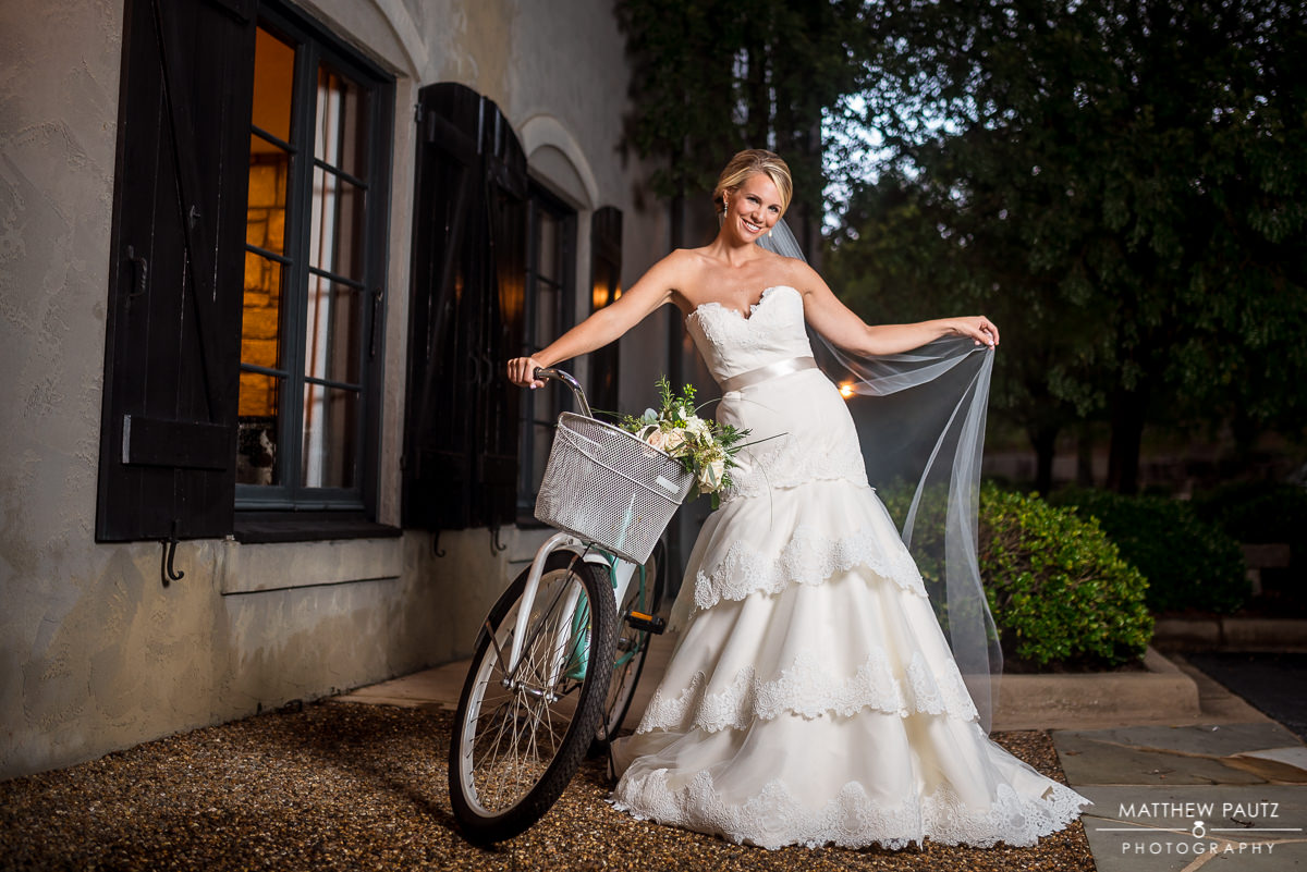 bride with dress and veil posing with bicycle