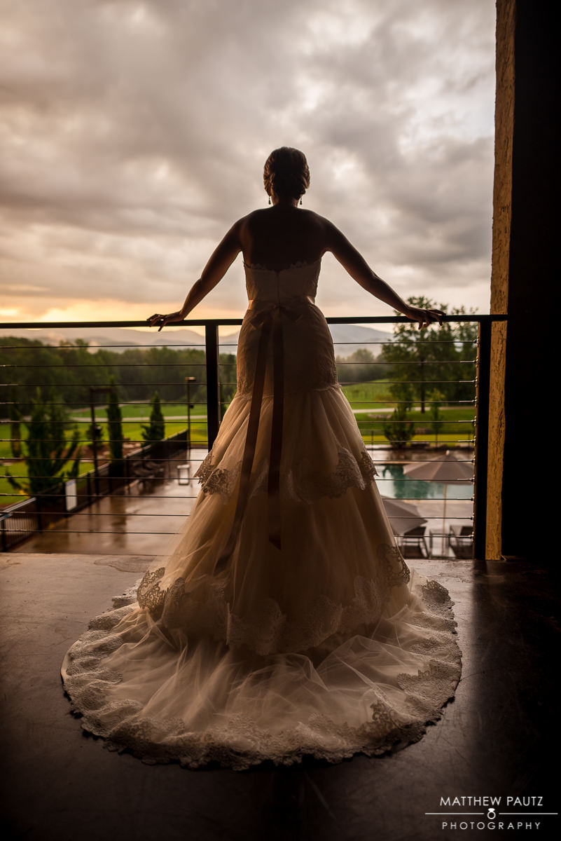 bride holding hotel railing watching sunset in the blue ridge mountains