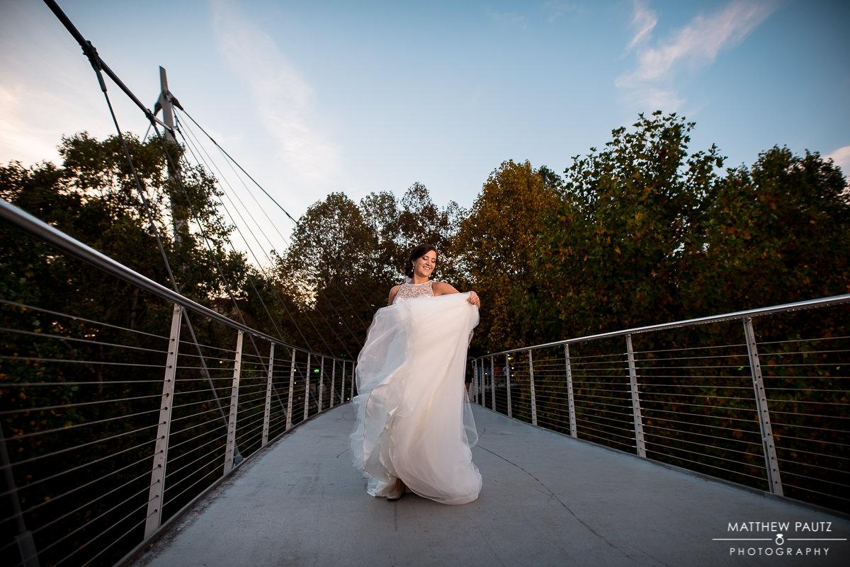 Bride twirling her dress on a bridge in Greenville
