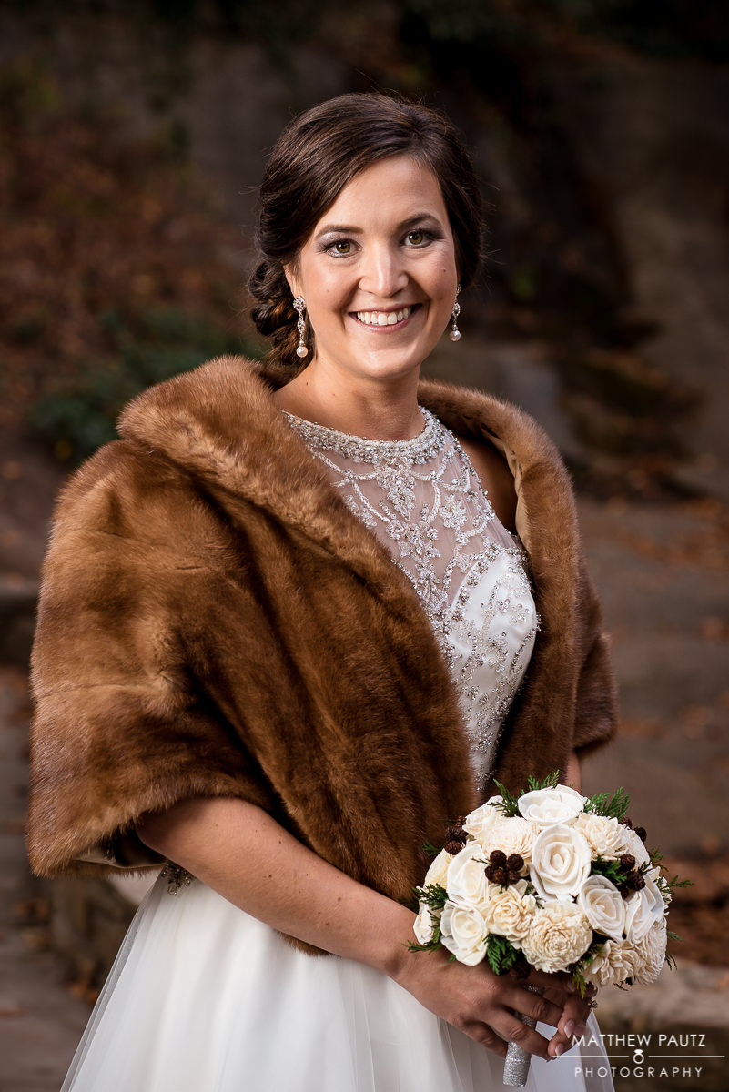 Bride in wedding dress holding flowers and wearing a brown fur wrap
