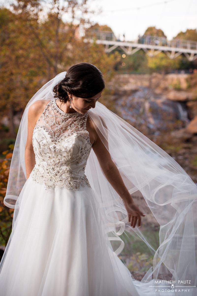 Bride adjusting her veil outside in park