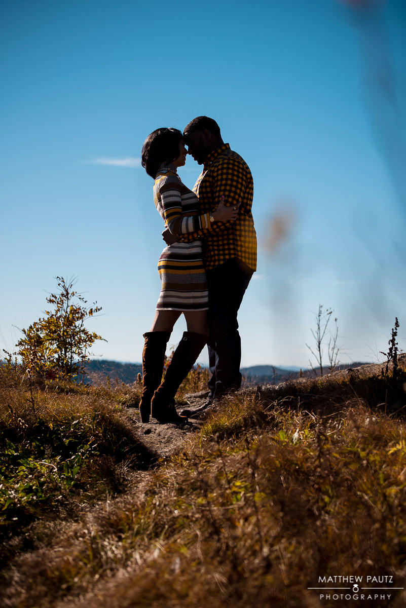 couple kissing in the mountains during Fall