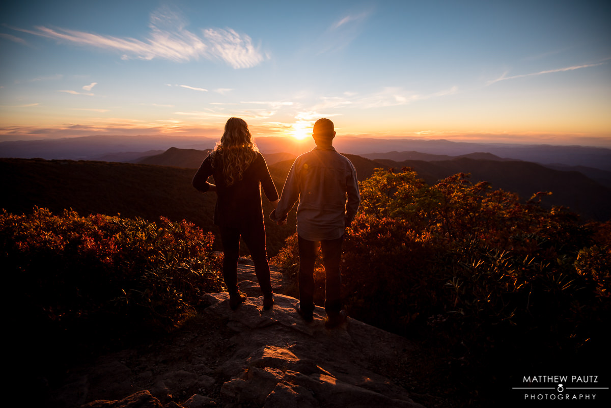 engaged couple holding hands at sunset in the blue ridge mountains
