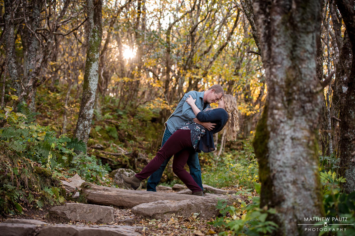 couple sharing a dramatic kiss in the woods during Fall