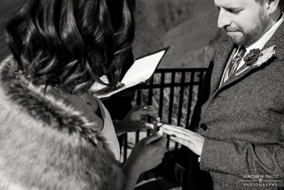 bride placing wedding ring on groom's hand