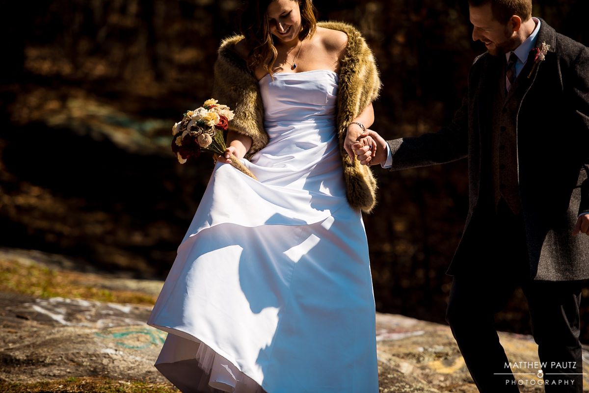 groom helping bride over rocks in mountains