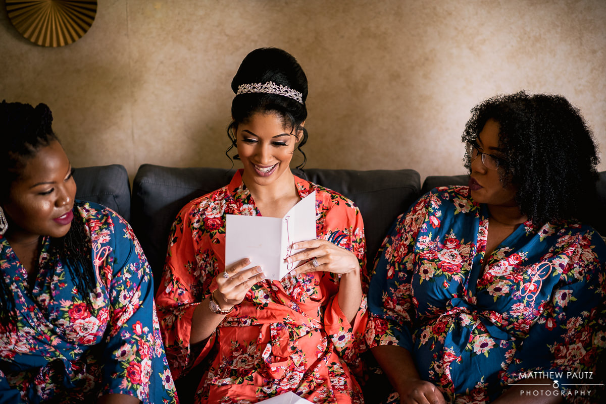 Bride in kimono reading card with bridesmaids before wedding