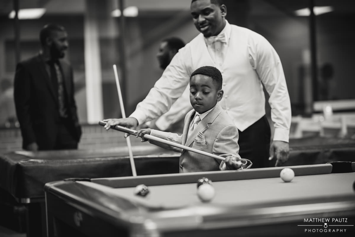 Groom helping young groomsman play pool before wedding