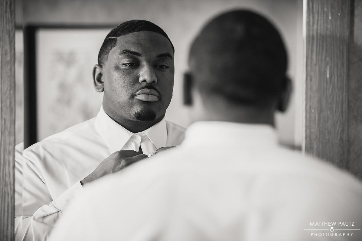 Groom adjusting tie in the mirror