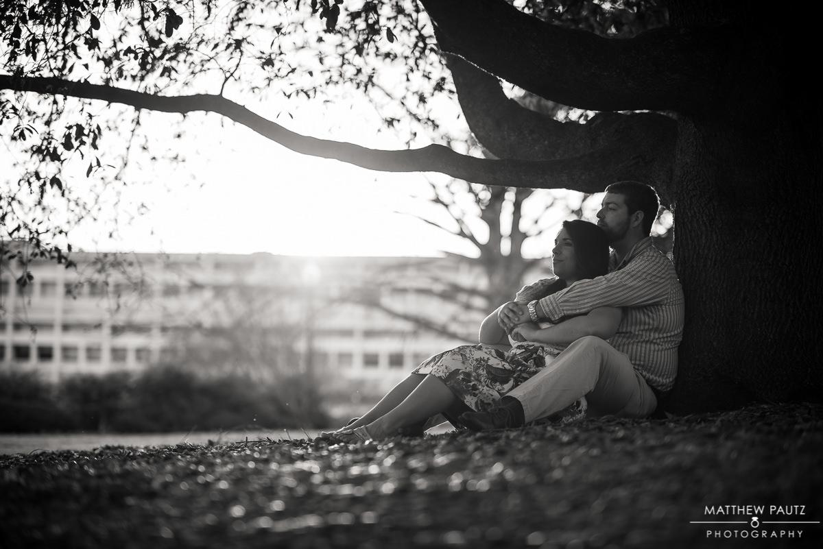 Engaged couple hugging under large oak tree on clemson campus
