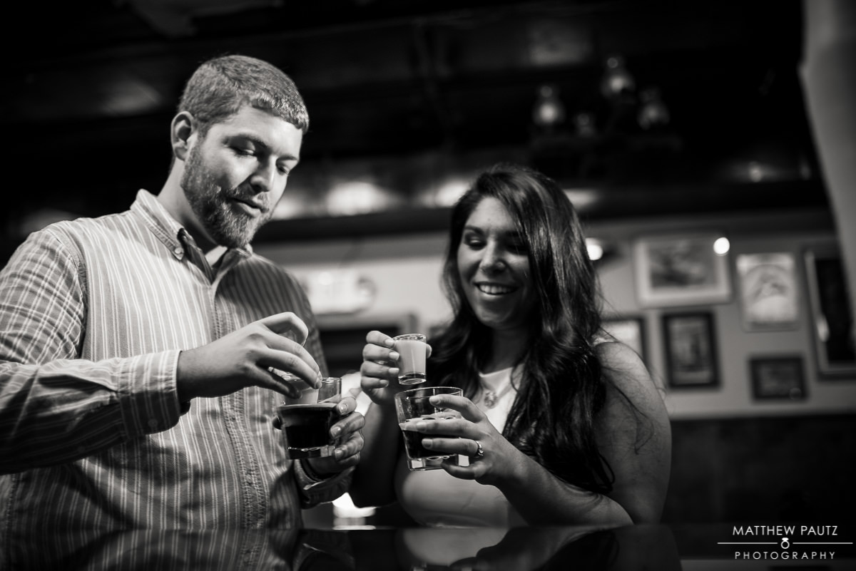 engaged couple taking shots in a bar