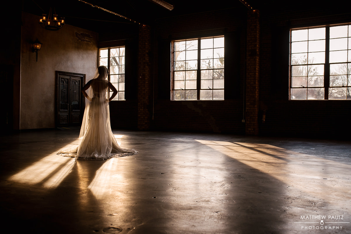 Bride in wedding dress standing in window light at Revel