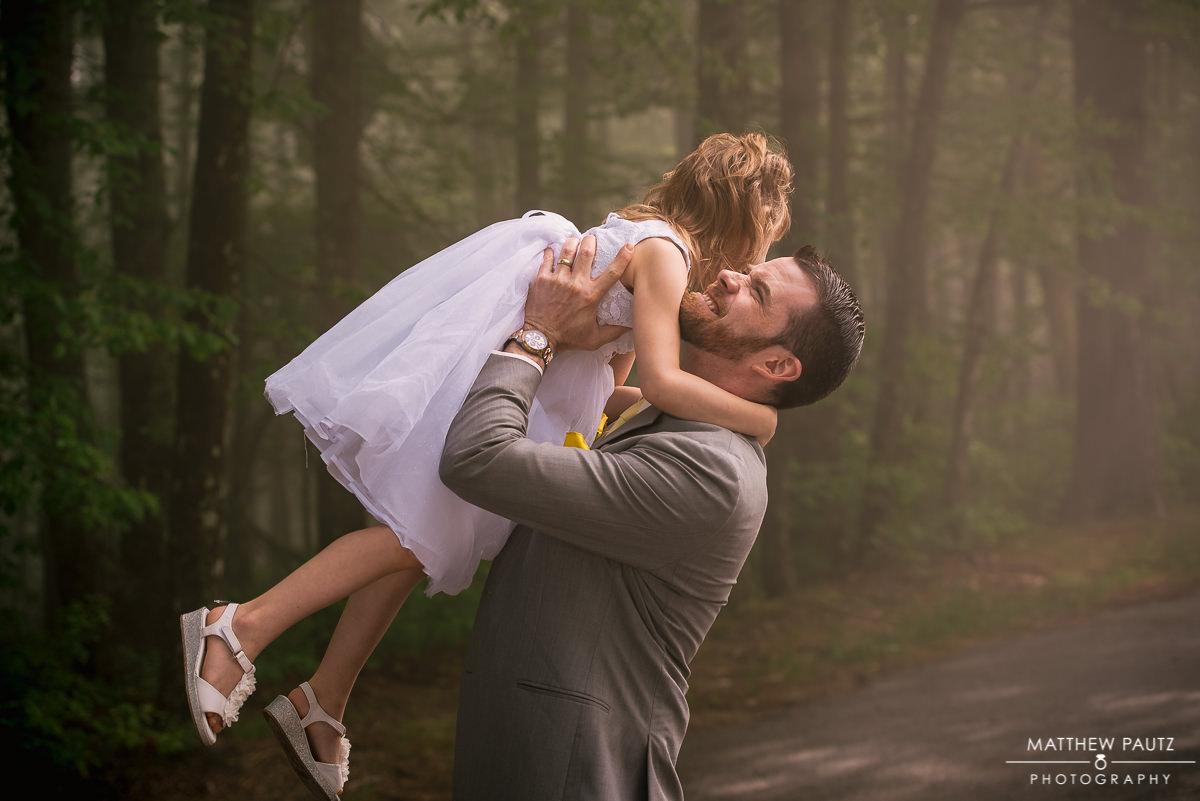 Groomsmen at wedding holding daughter above head