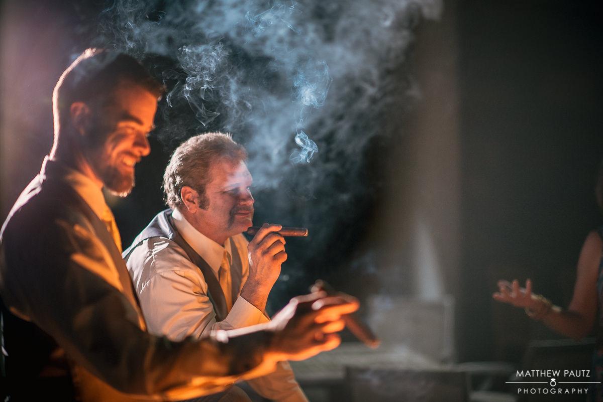 Groomsmen smoking cigars outside at night