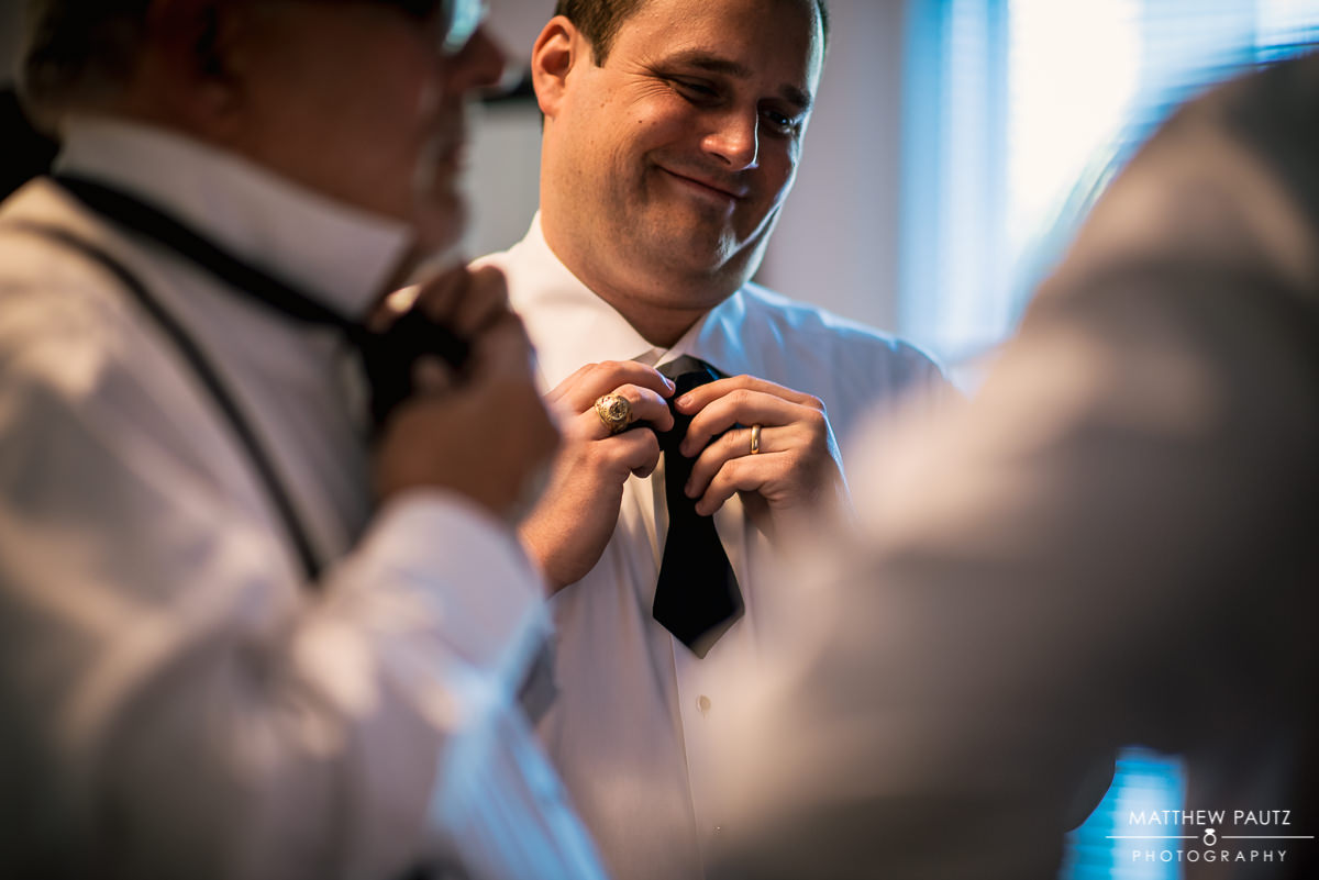 groomsmen tying bowties before wedding