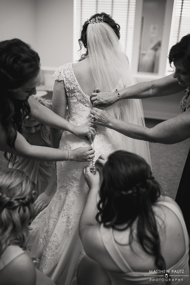 bridesmaids helping bride get her dress on at St Marys