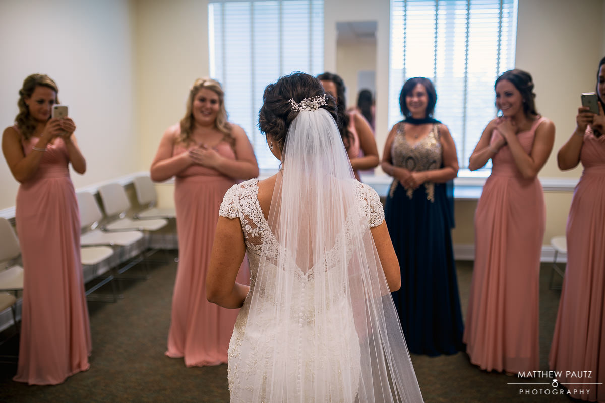 bridesmaids looking at bride after putting on dress