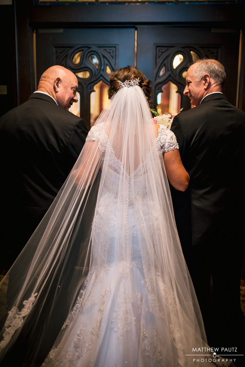 bride being led down aisle escorted by both dads