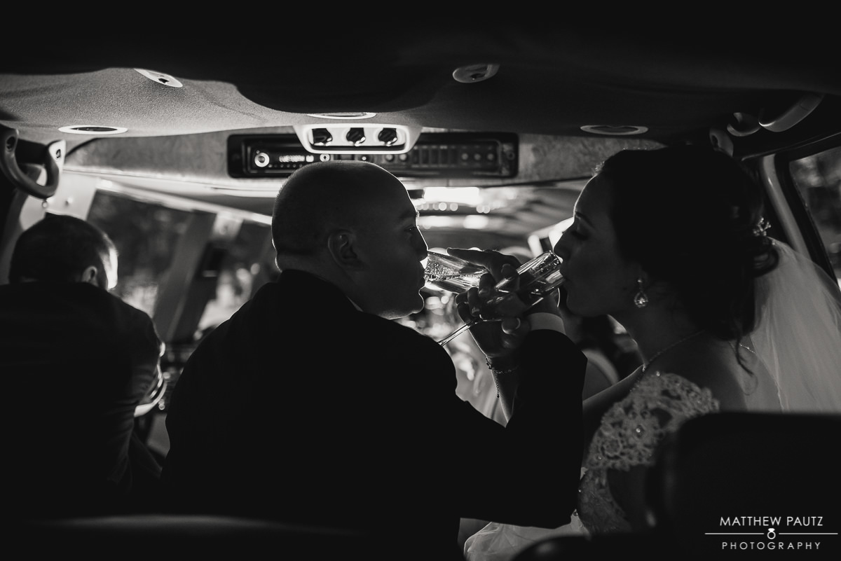 bride and groom drinking champagne in the back of a limo after wedding