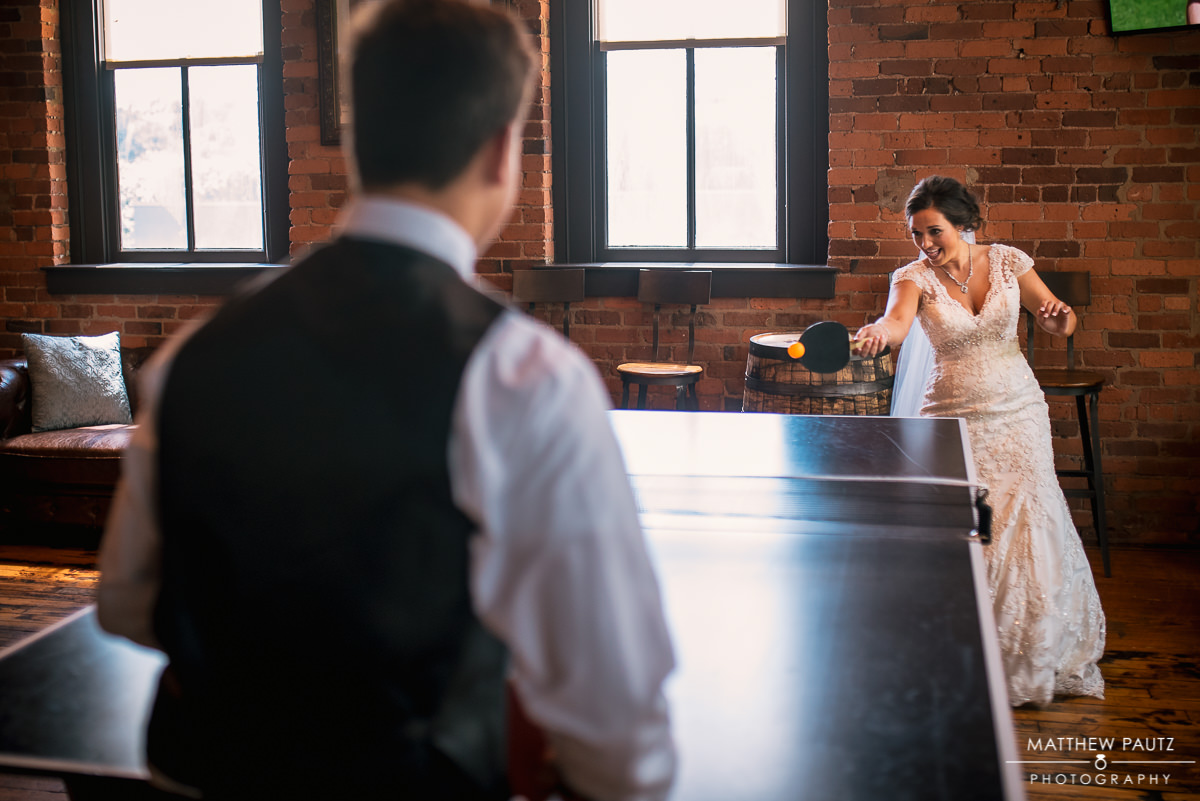 bride playing ping pong after wedding at brazwell's pub
