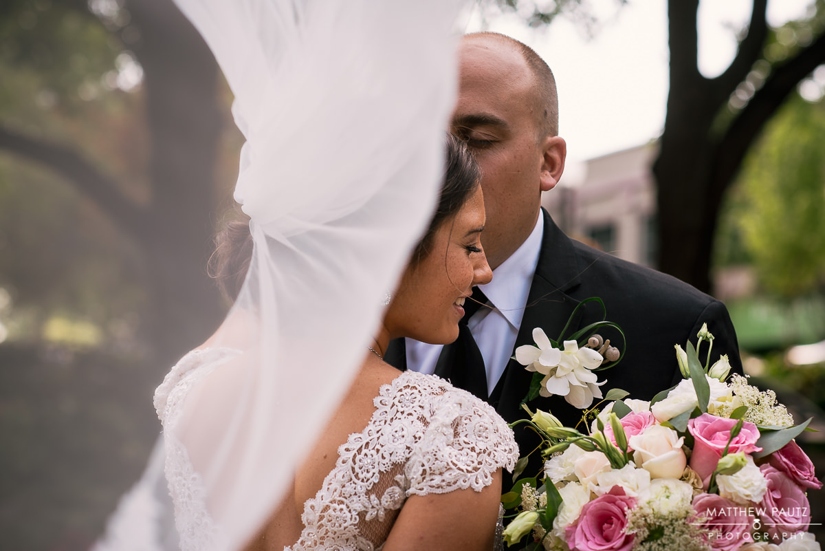 bride and groom kissing with wedding veil blowing in wind