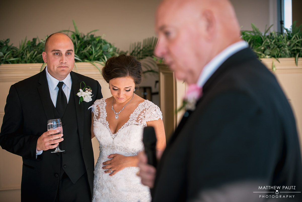 bride and groom look on while father of bride gives reception speech