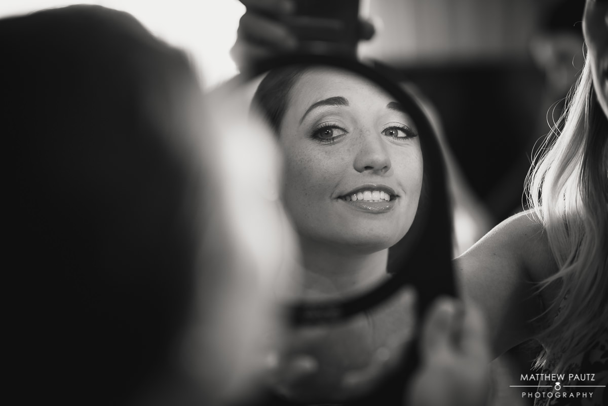 bride looking at her reflection through a mirror while getting ready for wedding