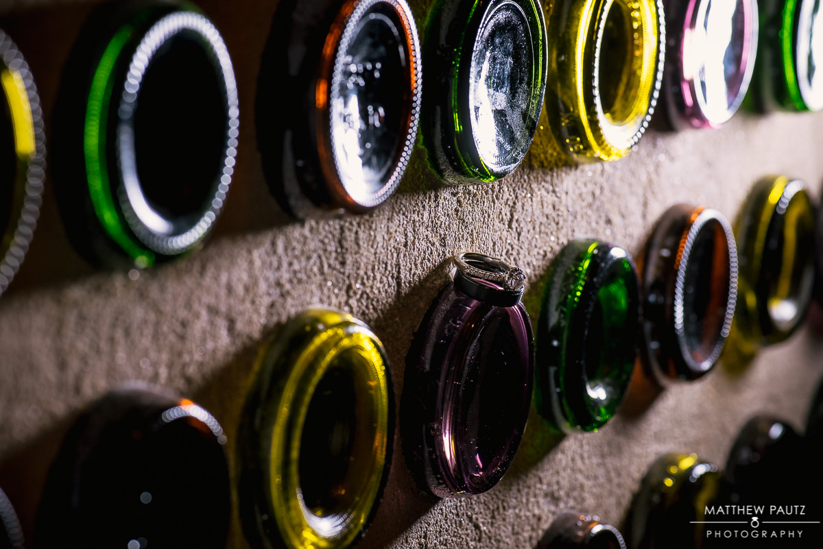 wedding rings on top of wine bottles