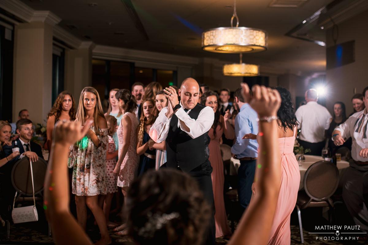 groom dancing with garter at wedding reception