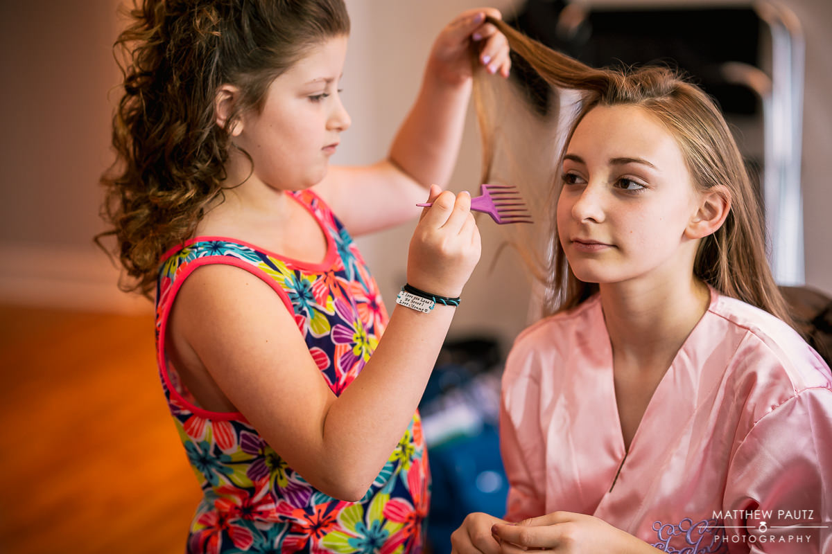 bridesmaid getting hair styled by flower girl