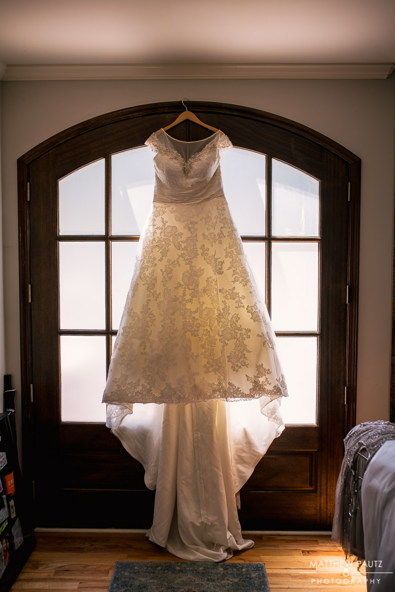 wedding dress hanging in frosted glass doorway