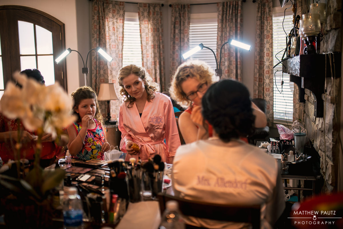 bridesmaids watching stylist apply makeup to bride before wedding