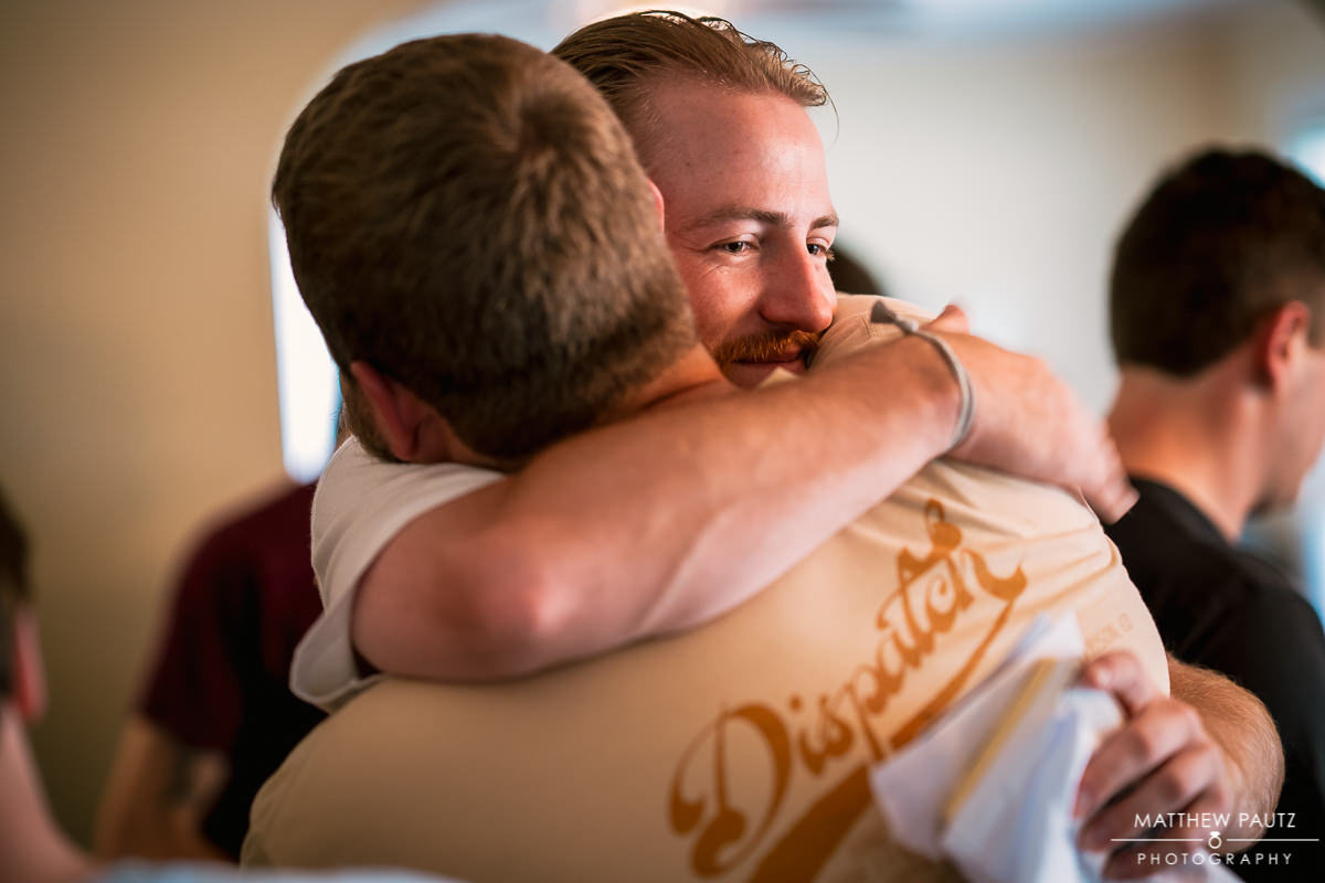 groomsman hugging groom while getting ready