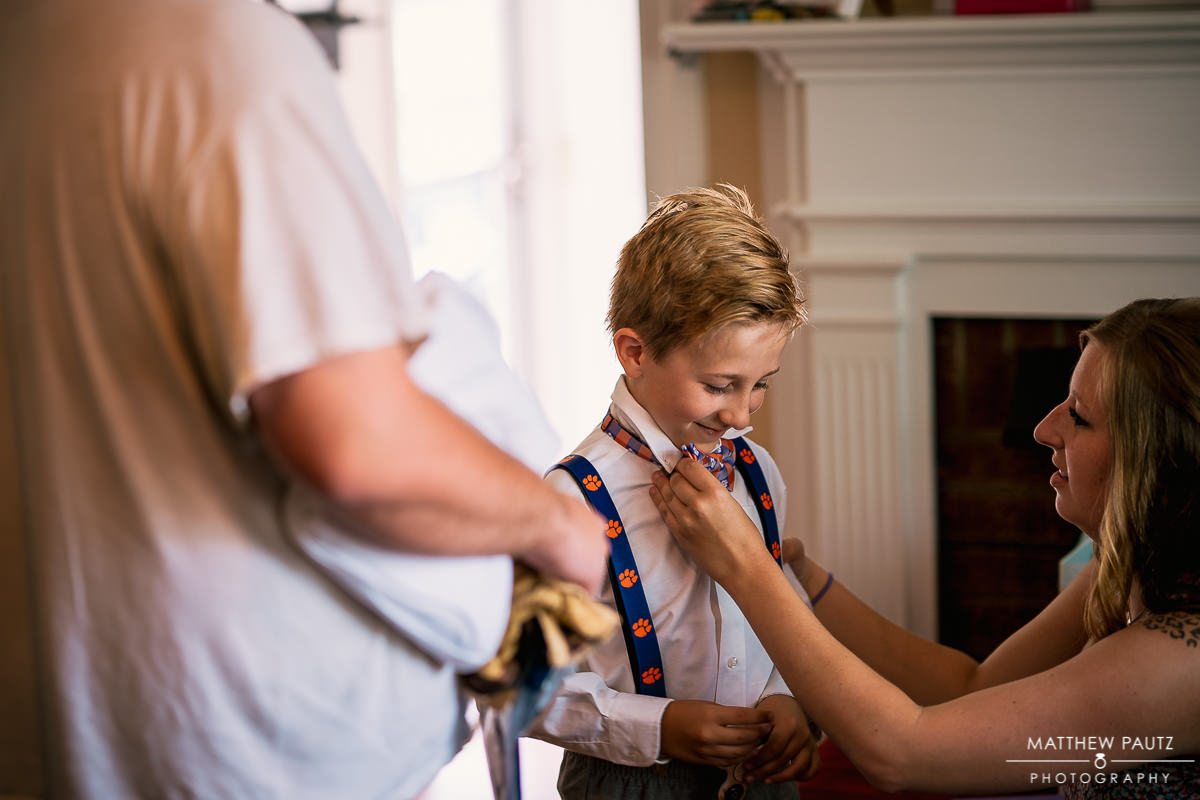 ring bearer with clemson suspenders before wedding ceremony