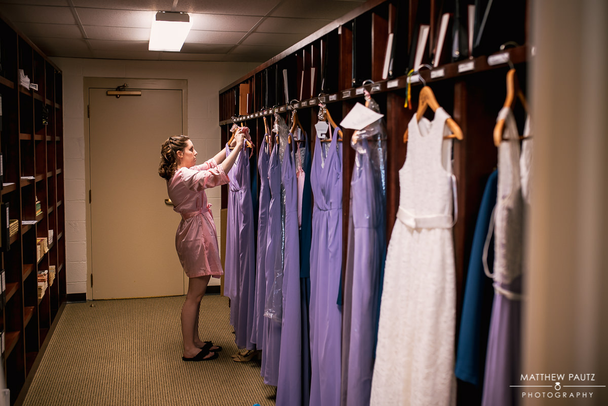 bridesmaid hanging up dresses at church